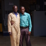 Technician of Musasa's new,modern dry mill poses here with the manager of Musasa, Ruli